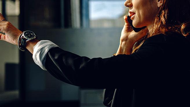 IT-ansatt ser på lønnsoversikt med hun snakker i mobilen