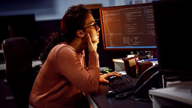 Kvinnelig IT-student foran en skjerm med kodespråk