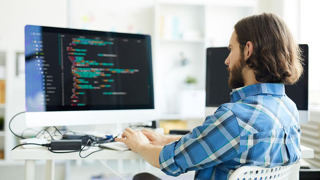 Frilans IT-konsulent som programmerer på skjerm