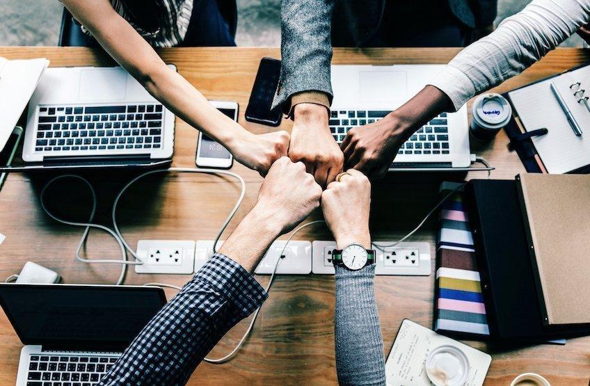 IT studenter rekker hånden mot hverandre