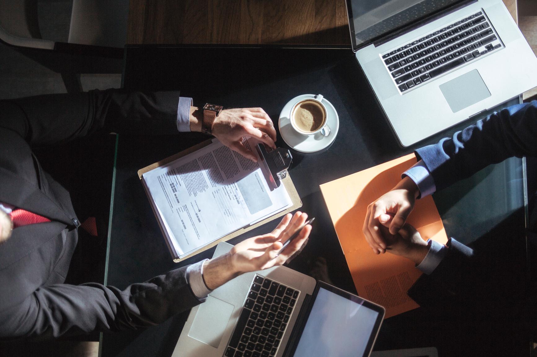 To menn som sitter i et møte med laptop pog dokumenter