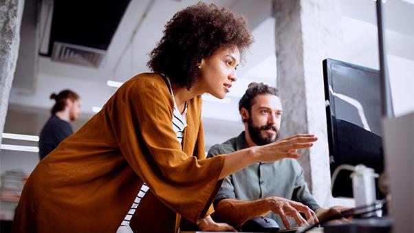 Prosjektleder som snakker og viser en medarbeider foran skjerm