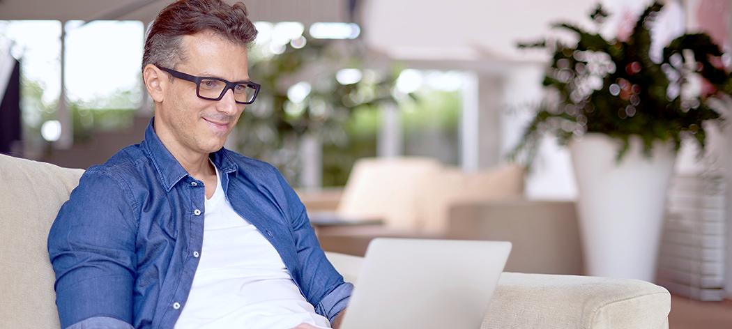 it-konsulent arbeider med laptop hjemme i sofa